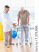 Senior man on zimmer frame with therapist. Стоковое фото, агентство Wavebreak Media / Фотобанк Лори