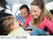 Parents securing baby in the car seat. Стоковое фото, агентство Wavebreak Media / Фотобанк Лори