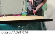 Купить «Столяр вкручивает саморезы электрическим шуруповертом для крепления ножек стола», видеоролик № 7391074, снято 10 февраля 2015 г. (c) Кекяляйнен Андрей / Фотобанк Лори