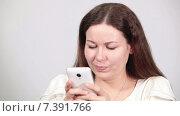 Купить «Красивая девушка быстро набирает смс на мобильном телефоне. используя два больших пальца, серый фон», видеоролик № 7391766, снято 8 марта 2015 г. (c) Кекяляйнен Андрей / Фотобанк Лори