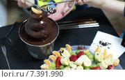 Тарелка с нарезанными фруктами рядом с шоколадным фонтаном, руки с вилками. Стоковое видео, видеограф Кекяляйнен Андрей / Фотобанк Лори