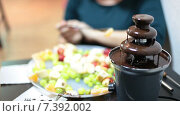 Женщина ест фрукты на вилке, окуная в жидкий шоколад в фонтане. Стоковое видео, видеограф Кекяляйнен Андрей / Фотобанк Лори