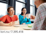 happy young women drinking tea or coffee at cafe. Стоковое фото, фотограф Syda Productions / Фотобанк Лори