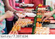 Купить «close up of hands with tongs taking sushi», фото № 7397634, снято 7 февраля 2015 г. (c) Syda Productions / Фотобанк Лори