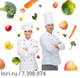 Купить «happy chef couple or cooks over food background», фото № 7398974, снято 7 марта 2015 г. (c) Syda Productions / Фотобанк Лори