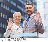 Купить «smiling businessmen standing over office building», фото № 7399170, снято 19 августа 2014 г. (c) Syda Productions / Фотобанк Лори