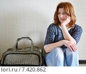 Купить «Грустная женщина сидит возле стены с чемоданом», фото № 7420862, снято 30 апреля 2015 г. (c) Володина Ольга / Фотобанк Лори