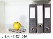 Купить «Три папки для документов, ежедневник и яблоко на полке», фото № 7421546, снято 25 февраля 2015 г. (c) Elena Molodavkina / Фотобанк Лори