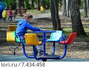 Купить «Мальчик-подросток катается один на карусели в городском парке», эксклюзивное фото № 7434458, снято 9 мая 2015 г. (c) Александр Замараев / Фотобанк Лори