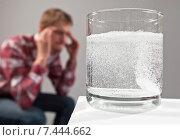 Стакан с шипучей таблеткой и водой на фоне мужчины, который держится руками за голову. Мигрень. Стоковое фото, фотограф Alexey Matushkov / Фотобанк Лори