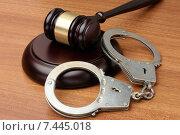 Купить «Судейский молоток и наручники лежат на деревянном столе», фото № 7445018, снято 30 апреля 2015 г. (c) Денис Ларкин / Фотобанк Лори