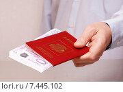 Купить «Мужская рука протягивает заграничный паспорт РФ с вложенными купюрами евро (фокус на деньгах)», фото № 7445102, снято 17 мая 2015 г. (c) Анна Менщикова / Фотобанк Лори