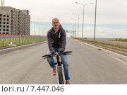 Велосипедист едет по новой строящейся пустынной улице (2015 год). Стоковое фото, фотограф Ивашков Александр / Фотобанк Лори