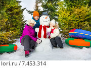 Счастливые дети сидят около снеговика зимой в лесу. Стоковое фото, фотограф Сергей Новиков / Фотобанк Лори