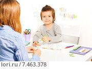 Веселый мальчик сидит за столом перед преподавателем и раскрашивает геометрические фигуры, фото № 7463378, снято 15 марта 2015 г. (c) Сергей Новиков / Фотобанк Лори