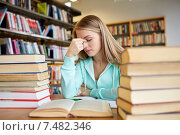 bored student or young woman with books in library. Стоковое фото, фотограф Syda Productions / Фотобанк Лори