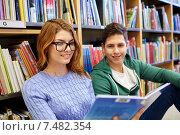 Купить «close up of happy students reading book in library», фото № 7482354, снято 6 марта 2015 г. (c) Syda Productions / Фотобанк Лори