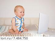 Ребенок с ноутбуком сидит на кровати (2015 год). Редакционное фото, фотограф Maria Siurtukova / Фотобанк Лори