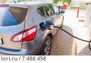 Купить «Легковой автомобиль заправляется бензином на автозаправочной станции», фото № 7488458, снято 21 июля 2018 г. (c) FotograFF / Фотобанк Лори