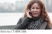 Купить «Девушка с длинными кудрявыми волосами разговаривает по мобильному телефону на ветру», видеоролик № 7494166, снято 5 мая 2015 г. (c) Кекяляйнен Андрей / Фотобанк Лори