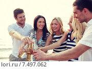 Купить «smiling friends clinking bottles on beach», фото № 7497062, снято 13 июля 2014 г. (c) Syda Productions / Фотобанк Лори