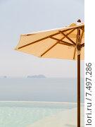 Купить «view from infinity edge pool with parasol to sea», фото № 7497286, снято 14 февраля 2015 г. (c) Syda Productions / Фотобанк Лори