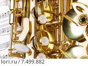 Купить «Блестящий золотой саксофон лежит на нотных листах (фрагмент)», фото № 7499882, снято 23 февраля 2015 г. (c) Сергей Новиков / Фотобанк Лори