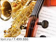 Купить «Виолончель и блестящий золотой саксофон лежат на нотных листах», фото № 7499886, снято 23 февраля 2015 г. (c) Сергей Новиков / Фотобанк Лори