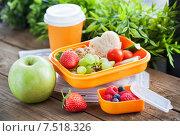 Ланч-бокс (коробка для завтрака, пикника или перекуса) с бутербродом, печеньем, свежими овощами и фруктами и стакан с кофе на заднем плане. Стоковое фото, фотограф Ekaterina Smirnova / Фотобанк Лори