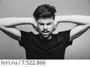 Купить «Мне нужна тишина. Молодой человек в футболке закрывает уши руками», фото № 7522866, снято 30 апреля 2015 г. (c) Константин Колосов / Фотобанк Лори
