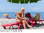 Счастливая симпатичная блондинка сидит на шезлонге на галечном пляже, фото № 7525578, снято 10 июля 2013 г. (c) Евгений Ткачёв / Фотобанк Лори