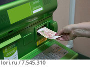 Человек (женщина) вставляет денежную купюру в слот банкомата. Стоковое фото, фотограф Игорь Травкин / Фотобанк Лори