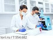 Купить «scientists with clipboard and microscope in lab», фото № 7554682, снято 4 декабря 2014 г. (c) Syda Productions / Фотобанк Лори