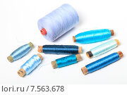 Купить «Катушки с голубыми и синими нитками на белом фоне», эксклюзивное фото № 7563678, снято 14 июня 2015 г. (c) Яна Королёва / Фотобанк Лори