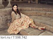 Купить «Молодая красивая девушка в юбке с цветочным узором сидит на каменных ступенях», фото № 7598742, снято 15 ноября 2013 г. (c) Елена Вакуленчик / Фотобанк Лори