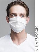 Купить «Молодой мужчина в медицинской маске смотрит в сторону», фото № 7604294, снято 9 июня 2015 г. (c) Дмитрий Булин / Фотобанк Лори