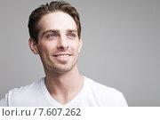 Купить «Счастливый молодой мужчина в белой футболке на сером фоне», фото № 7607262, снято 9 июня 2015 г. (c) Дмитрий Булин / Фотобанк Лори