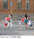 Купить «Молодые женщины переводят детей за руки по пешеходному переходу в городе», эксклюзивное фото № 7609502, снято 19 февраля 2019 г. (c) Елена Осетрова / Фотобанк Лори