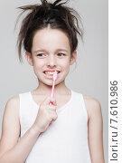 Купить «Маленькая девочка чистит зубы на сером фоне», фото № 7610986, снято 13 мая 2015 г. (c) Дмитрий Булин / Фотобанк Лори