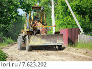Грейдер едет по сельской дороге летом на фоне зелени (2015 год). Редакционное фото, фотограф Витолина Бычок / Фотобанк Лори
