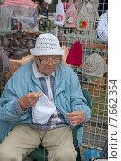 Купить «Пожилая женщина вяжет и продает чепчики на ярмарке народных промыслов», эксклюзивное фото № 7662354, снято 11 июля 2015 г. (c) Svet / Фотобанк Лори