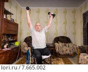 Пожилой мужчина в инвалидной коляске занимается с гантелями у себя дома. Стоковое фото, фотограф Вячеслав Николаенко / Фотобанк Лори