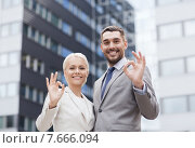Купить «smiling businessmen standing over office building», фото № 7666094, снято 19 августа 2014 г. (c) Syda Productions / Фотобанк Лори