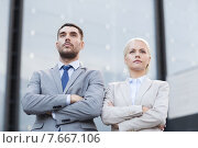 Купить «serious businessmen standing over office building», фото № 7667106, снято 19 августа 2014 г. (c) Syda Productions / Фотобанк Лори