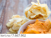 Купить «close up of potato crisps and corn nachos on table», фото № 7667902, снято 22 мая 2015 г. (c) Syda Productions / Фотобанк Лори