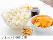 Купить «close up of popcorn and corn crisps or nachos», фото № 7668518, снято 21 мая 2015 г. (c) Syda Productions / Фотобанк Лори