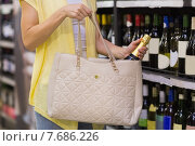Купить «Pretty woman putting a champagne bottle in her bag», фото № 7686226, снято 21 января 2015 г. (c) Wavebreak Media / Фотобанк Лори