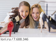 Two excited women looking at heel shoes. Стоковое фото, агентство Wavebreak Media / Фотобанк Лори