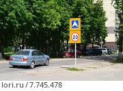 Купить «Автомобиль преодолевает лежачий полицейский возле дорожных знаков Искусственная неровность и Ограничение максимальной скорости в городе на фоне дома и деревьев», эксклюзивное фото № 7745478, снято 12 июня 2015 г. (c) Наталья Горкина / Фотобанк Лори