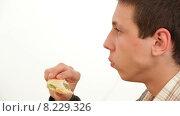 Купить «Мужчина ест гамбургер», видеоролик № 8229326, снято 26 июня 2015 г. (c) Tatiana Kravchenko / Фотобанк Лори